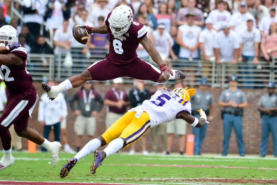 Oct 19, 2019; Starkville, MS, USA; Mississippi State Bulldogs running back Kylin Hill (8) hurdles Louisiana State Tigers  cornerback Kary Vincent Jr. (5) during the first quarter at Davis Wade Stadium. Mandatory Credit: Matt Bush-USA TODAY Sports