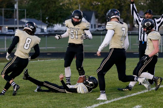 Delphi's Riley Lowder (40) slides into the end zone to score a honorary touchdown as his teammates celebrate around him.