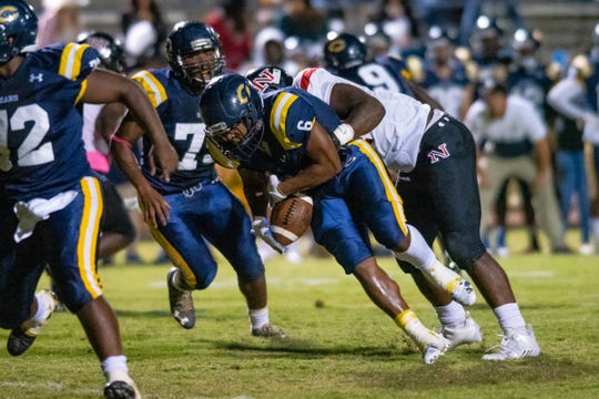 Carencro High's Dontae Darjean holds onto the ball while being taken down as the Carencro High Golden Bears take on the Northside High Vikings during their homecoming game on Friday, Oct. 18, 2019.