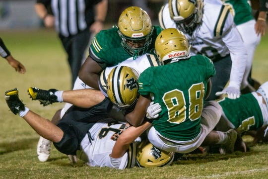 Acadiana High's defense takes down the runner during the play as the Acadiana High Wreckin' Rams take on the New Iberia High Yellowjackets during their homecoming game on Friday, Oct. 18, 2019.