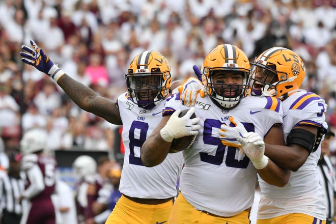 Oct 19, 2019; Starkville, MS, USA; Louisiana State Tigers  defensive lineman Rashard Lawrence (90) reacts with  safety JaCoby Stevens (3) and linebacker Patrick Queen (8) after a fumble by the Mississippi State Bulldogs during the second quarter at Davis Wade Stadium. Mandatory Credit: Matt Bush-USA TODAY Sports