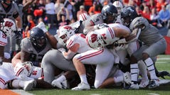 Wisconsin fullback John Chenal is stopped short of the goal line by Illinois defensive back Stanley Green during the fourth quarter, forcing a field goal.