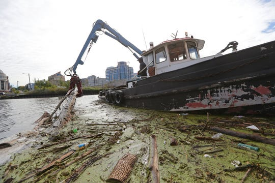 David Randolph, a Port of Milwaukee maintenance technician, works on clearing logs and debris from the Milwaukee River near the East Knapp Street bridge Monday, Oct. 14, 2019. Heavy rains, high water levels and the loss of the Estabrook Dam have caused an increase in logs and debris making their way downriver, causing problems for boaters and cleanup crews.