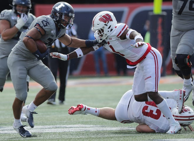 Illinois running back Dre Brown gets past Wisconsin cornerback Faion Hicks during a run in the fourth quarter Saturday.