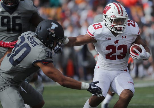 Wisconsin running back Jonathan Taylor stiff-arms Illinois defensive back Sydney Brown before fumbling the ball during the fourth quarter. In the first quarter Taylor reached 5,000 yards rushing.