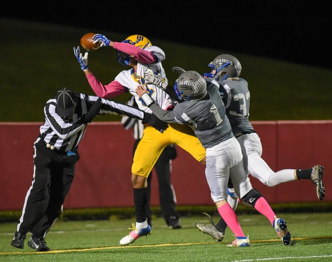Milwaukee King's Jerry Cross catches a pass for a two-point conversation over Milwaukee Reagan's Keagan O'Keefe (1) and Christian Oliverria (32) and an official  in the Milwaukee City Conference football championship game Friday, October 18, 2019, at South Stadium.