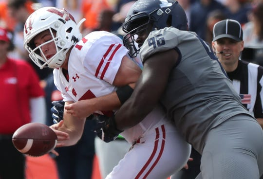 Wisconsin quarterback Jack Coan throws an incomplete pass while wrapped up by llinois defensive lineman Tymir Oliver Saturday. The Badgers dropped in the polls after the shocking loss at Illinois.