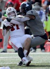 Wisconsin running back Garrett Groshek is stuffed at the line by Illinois linebacker Dele Harding in the fourth quarter.