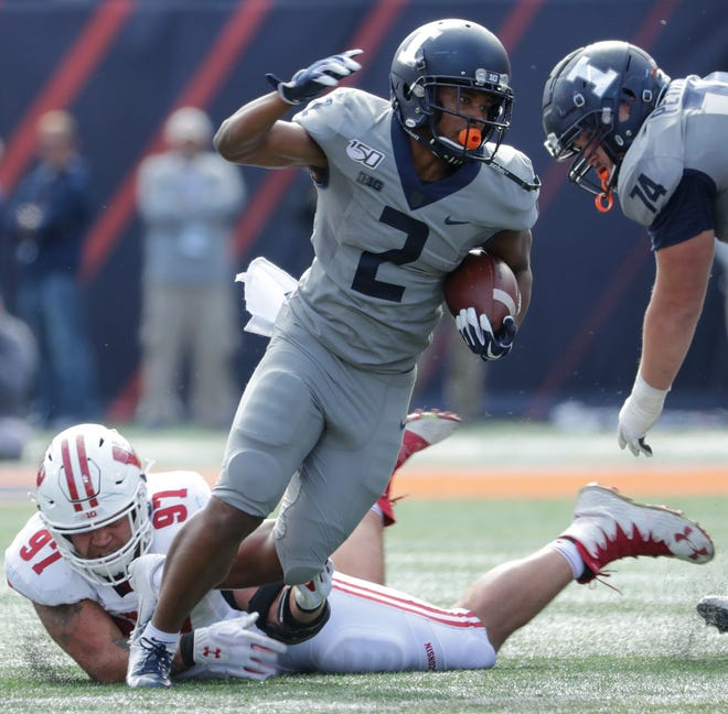 Illinois running back Reggie Corbin eludes the grasp Wisconsin defensive end Isaiahh Loudermilk in the fourth quarter of their 2019 matchup.