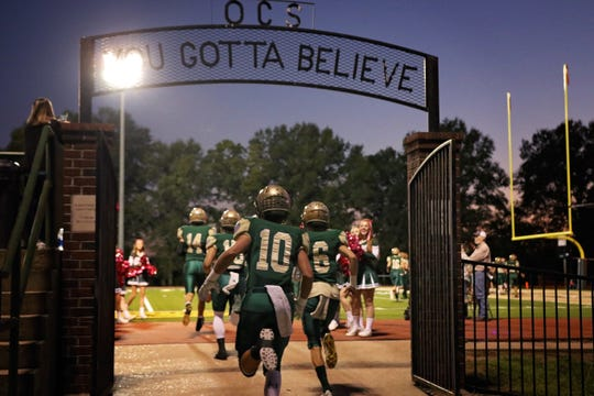 """The OCS Eagles pass through the """"You've Gotta Believe"""" gate towards Eagles Stadium. Head coach Steven Fitzhugh reminded them of that message against Calvary Baptist."""