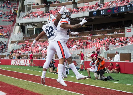 Auburn running back Malik Miller (32) and Auburn running back Jay Jay Wilson (42) celebrate Wilson's touchdown catch at Donald W. Reynolds Razorback Stadium in Fayetteville, Ark., on Saturday, Oct. 19, 2019. Auburn defeated Arkansas 51-10.