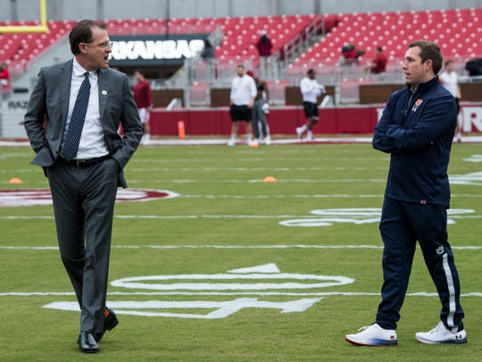 Auburn head coach Gus Malzahn and Auburn offensive coordinator Kenny Dillingham chat on the field at Donald W. Reynolds Razorback Stadium in Fayetteville, Ark., on Saturday, Oct. 19, 2019.