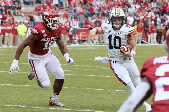 Oct 19, 2019; Fayetteville, AR, USA; Auburn Tigers quarterback Bo Nix (10) rushes for a touchdown run the first quarter against as Arkansas Razorbacks defensive lineman Mataio Soli (11) defends at Donald W. Reynolds Razorback Stadium. Mandatory Credit: Nelson Chenault-USA TODAY Sports