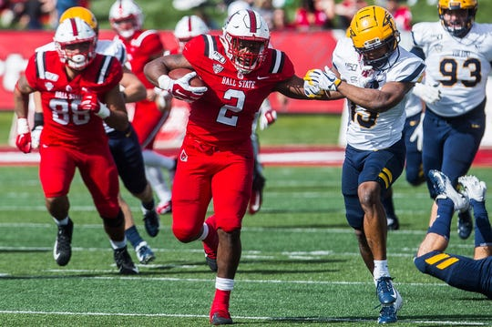Ball State's Caleb Huntley slips past Toledo's defense during their Homecoming game at Scheumann Stadium Saturday, Oct. 19, 2019.