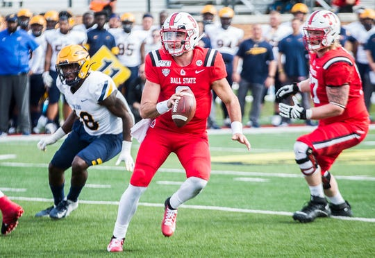 Ball State's Drew Plitt looks for an opening in Toledo's defense during their Homecoming game at Scheumann Stadium Saturday, Oct. 19, 2019.