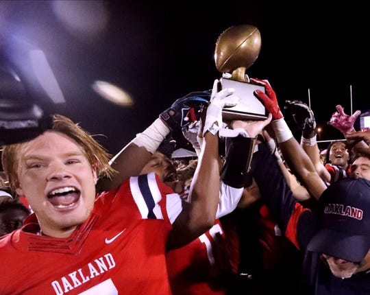 Oakland's quarterback Kody Sparks (7) puts his hand on the Friday Night Rivals Championship Trophy along with other Oakland players after beating Riverdale 31-17 the in the Battle of the Boro, on Friday, Oct. 18, 2019, at Oakland.
