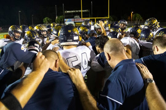 The Naples High football team prays after their win on Friday, Oct. 18, 2019, at Golden Gate High School. The Naples High won at Golden Gate, clinching its 10th straight district championship.