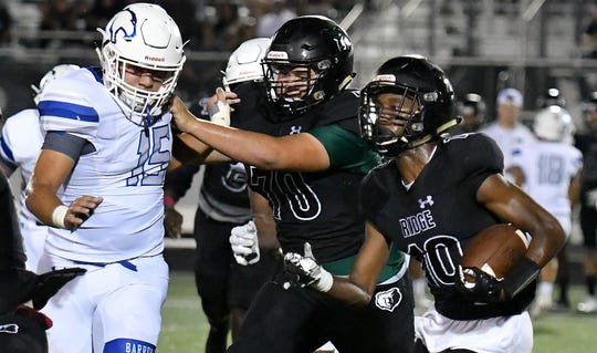 Palmetto Ridge High School Malique Dieudonne (10) finds some room to run with the help of a team make blocking Barron Collier High School Allan Hernandez (15) in their football matchup in Naples, Friday, Oct. 18, 2019. Chris Tilley/SPECIAL TO THE NAPLES DAILY NEWS