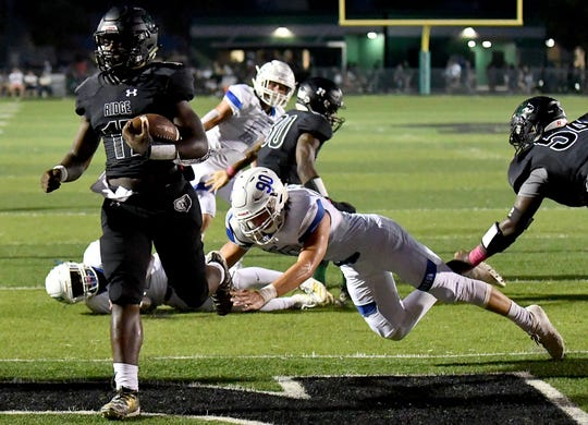 Palmetto Ridge High School Jaden Booker (17) runs the ball in for a touchdown with  Barron Collier High School in Calogero Carollo (90) trying to  make the tackel during their game Friday night in Naples, Friday, Oct. 18, 2019. Chris Tilley/SPECIAL TO THE NAPLES DAILY NEWS