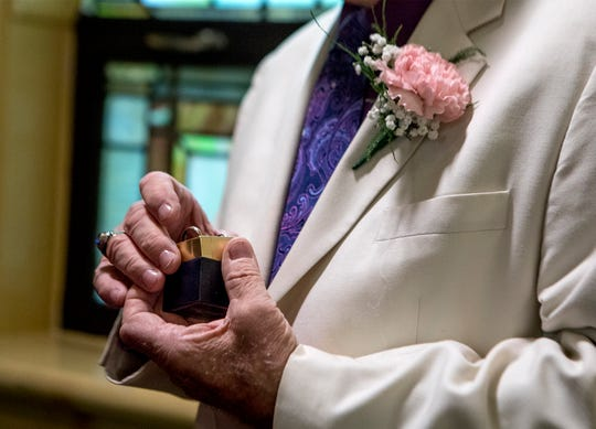 Bob Harvey dressed in a white sport coat with a pink carnation, pulls the wedding rings out before marrying Annette Callahan Saturday morning.