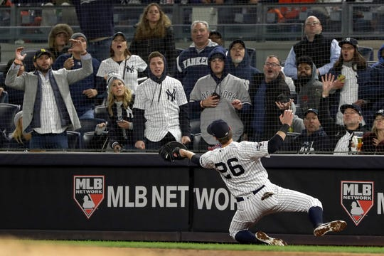 New York Yankees first baseman DJ LeMahieu (26) makes a catch on a pop up in foul territory by Houston Astros' Yuli Gurriel to end the top of the third inning of Game 5 of baseball's American League Championship Series, Friday, Oct. 18, 2019, in New York.