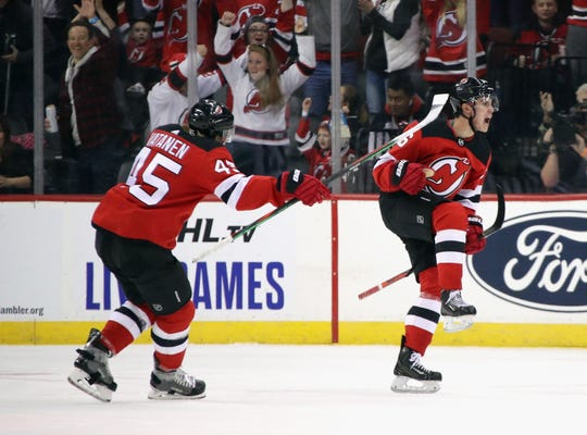 Jack Hughes #86 of the New Jersey Devils (R) celebrates his first NHL goal as he scores at 14:08 of the first period on the power-play against the Vancouver Canucks at the Prudential Center on October 19, 2019 in Newark, New Jersey.