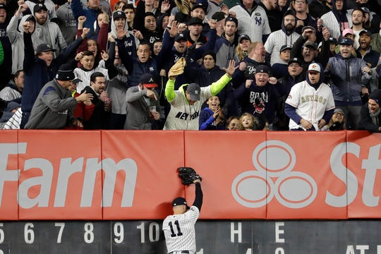 New York Yankees fans react after New York Yankees center fielder Brett Gardner (11) caught a deep fly ball by Houston Astros Robinson Chirinos at the wall to end the top of the sixth inning of Game 5 of baseball's American League Championship Series, Friday, Oct. 18, 2019, in New York.