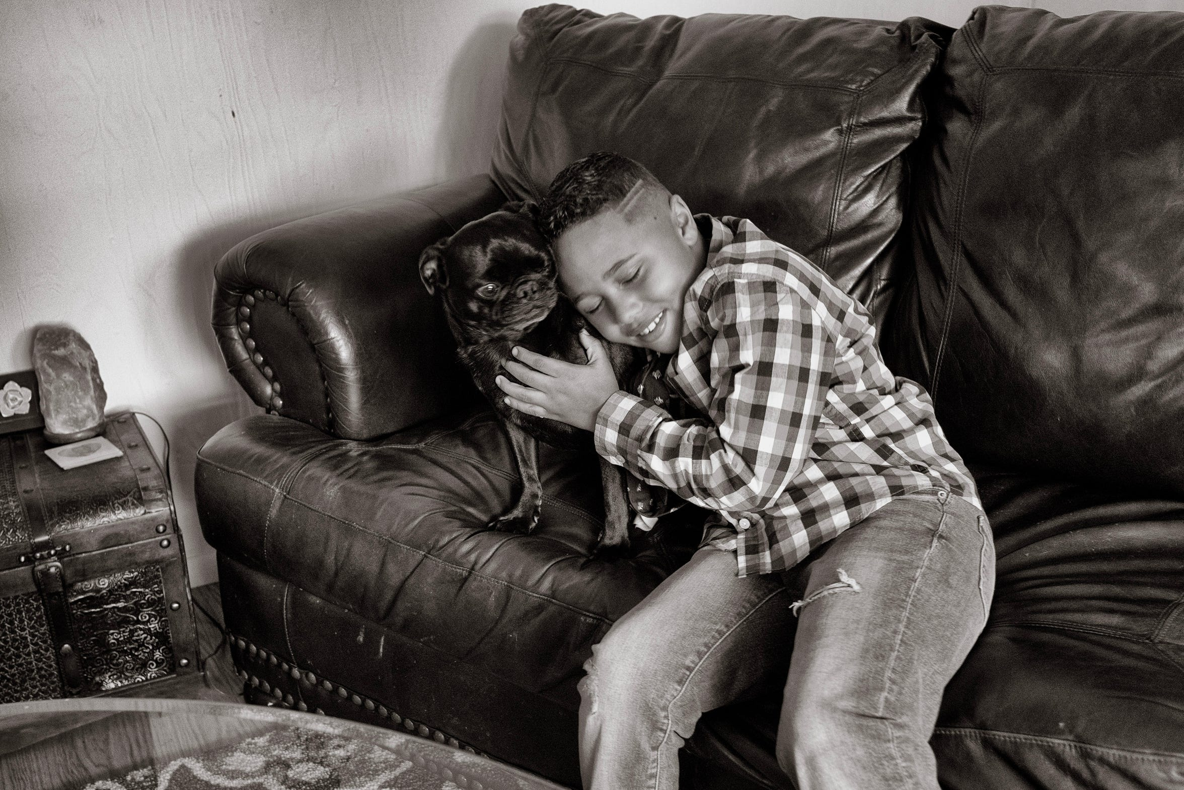 Jamari Nelson, 7, with Shadow. Jamari is close to the two-year-old pug, the two sometimes even share a bed.