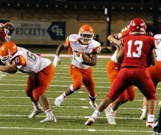 Artesia's Nathan Barrera runs through a hole during Friday's game against Roswell. Roswell won, 48-28.