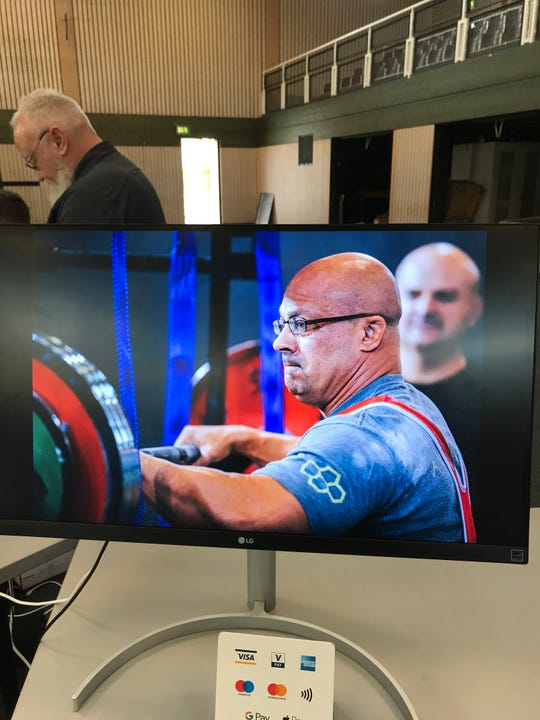 Kirtland Central athletic trainer Darrel Dryden, seen here on a video screen, won the IPL World Championships Masters Level I title Saturday in Leipzig, Germany. Dryden tallied a combined score of 1,417 in the squat, bench press and deadlift categories.