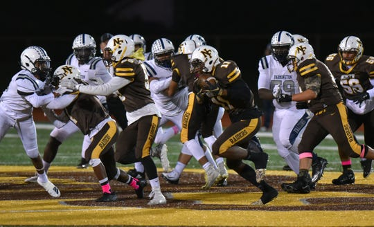 North Farmington Raider Myles Gresham carries the ball against cross-town rival Farmington on Oct. 17, 2019.