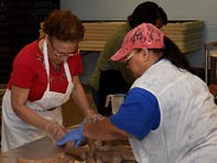 Fannie Simmons and Brenda Curtis cut the sausage into individual links.