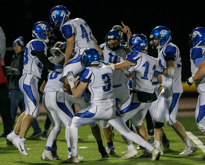 Oshkosh West players celebrate after an interception against Oshkosh North in October 2019. Assistant Duane Hartkopf has been named the interim head coach of the program.