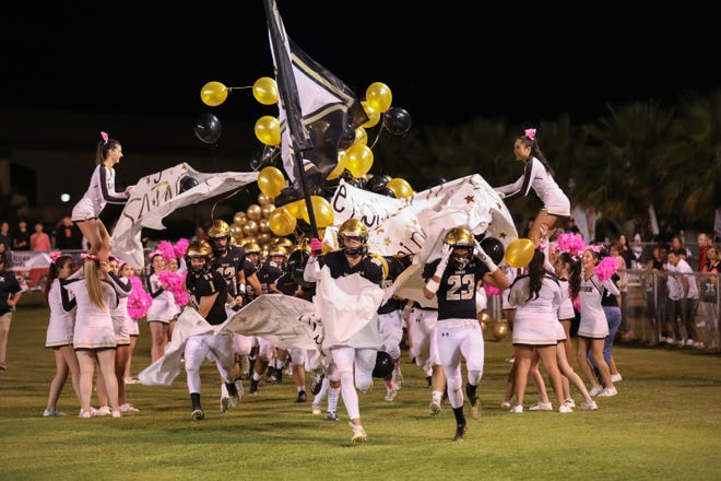 The Xavier Prep High School  football team races onto the field before their game against Shadow Hills on Oct. 18, 2019,
