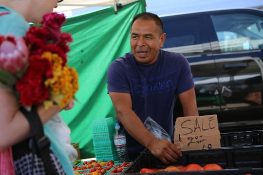 Mario Julian of Nest Farms talks to a customer at the Joshua Tree Certified Farmers' Market in Joshua Tree, Calif., on Saturday, October 19, 2019.