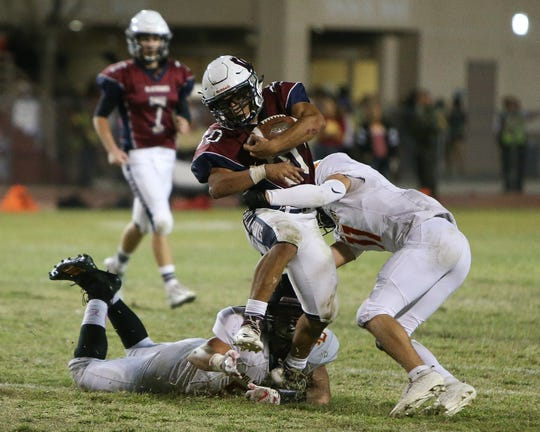 La Quinta running back Johnnie Lafayette tries to break free from a pair of Palm Desert tacklers during the first half Oct. 18, 2019.