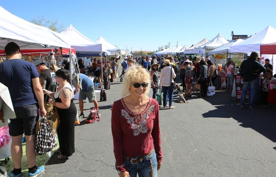 Joshua Tree Certified Farmers' Market owner and operator, Lori Herbel, center, walks around the market in Joshua Tree, Calif., on Saturday, October 19, 2019. Next Saturday the market celebrates its twelfth year in Joshua Tree.