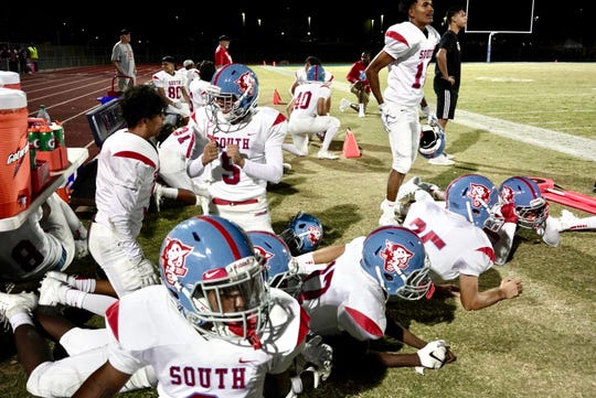 Players duck down at Betty Fairfax High School in Phoenix as multiple gunshots could be heard during game play Oct. 18, 2019.