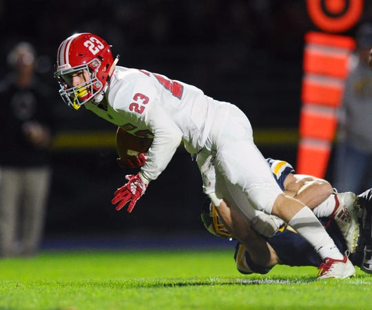 A-C's Evan Heilman (23) is pulled down by an Elco defender during first quarter action in  a game between the Annville-Cleona Dutchmen and the Elco Raiders on Friday Oct.18,2019 at Elco.