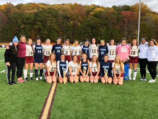 Senior members of the John Jay and Arlington High School field hockey teams pose together, with their coaches, before facing each other for the last time this season on Friday.
