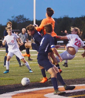Susquehannock's Aaron Filsinger looks on as the Warriors try to score against Dallastown goalie Gavin Conners. Susquehannock's Nathan Weldon is at right.