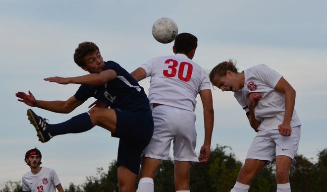 Susquehannock's Jonathan Lippy heads the ball while defended by Dallastown's Mitchell Groh, left.