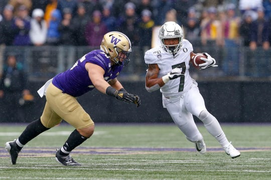 Oct 19, 2019; Seattle, WA, USA; Oregon Ducks running back CJ Verdell (7) carries the ball past Washington Huskies linebacker Ryan Bowman (55) during the first quarter at Husky Stadium. Mandatory Credit: Jennifer Buchanan-USA TODAY Sports