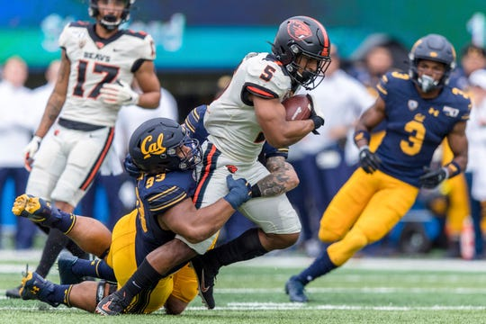 Oregon State wide receiver Kolby Taylor (5) is tackled by California  nose tackle Luc Bequette (93) in the second quarter of an NCAA college football game in Berkeley, Calif., Saturday, Oct. 19, 2019.
