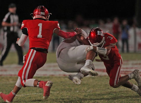 Davian Martinez, left, and Landon Book, right, tackle an opponent for Miles on Friday, Oct. 18, 2019.