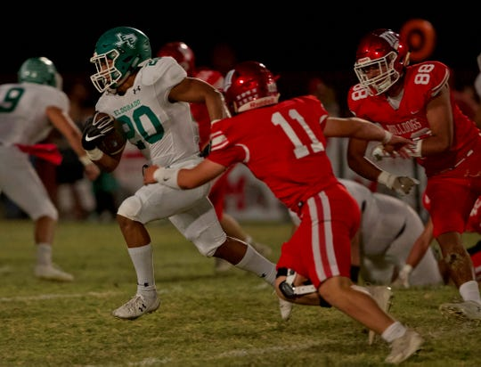 Elias Luna, left, rushes the ball for Eldorado on Friday, Oct. 18, 2019.