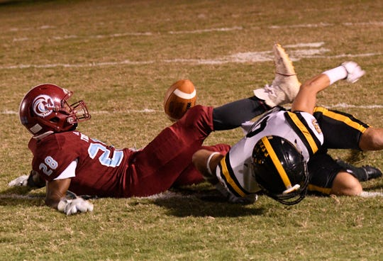 Neville's Andrew Cagle forces a fumble from Minden's Justin Richardson in a District 4-A contest Friday night.