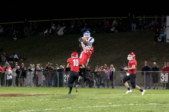 Fort Defiance's Addison Knicely hauls in a pass against the Riverheads defense Friday.