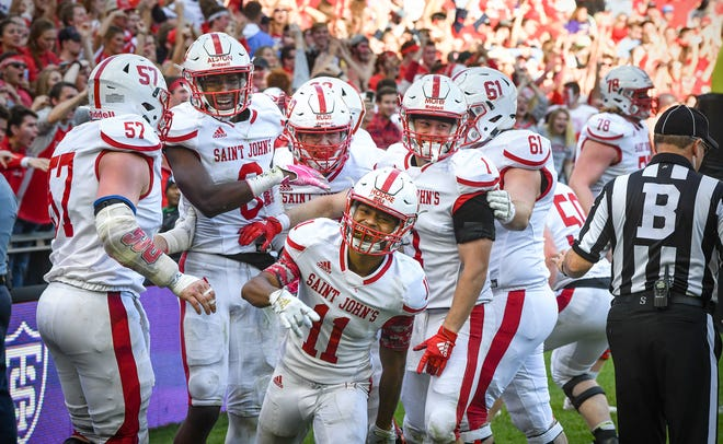 T.J. Hodge celebrates with teammates after a St. John's touchdown in the second half of the game Saturday, Oct. 19, 2019, at Allianz Field in St. Paul.
