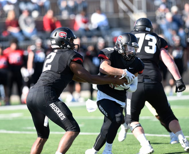 St. Cloud State quarterback Dwayne Lawhorn hands off to Tanner Teige Saturday, Oct. 19, 2019, at Husky Stadium.